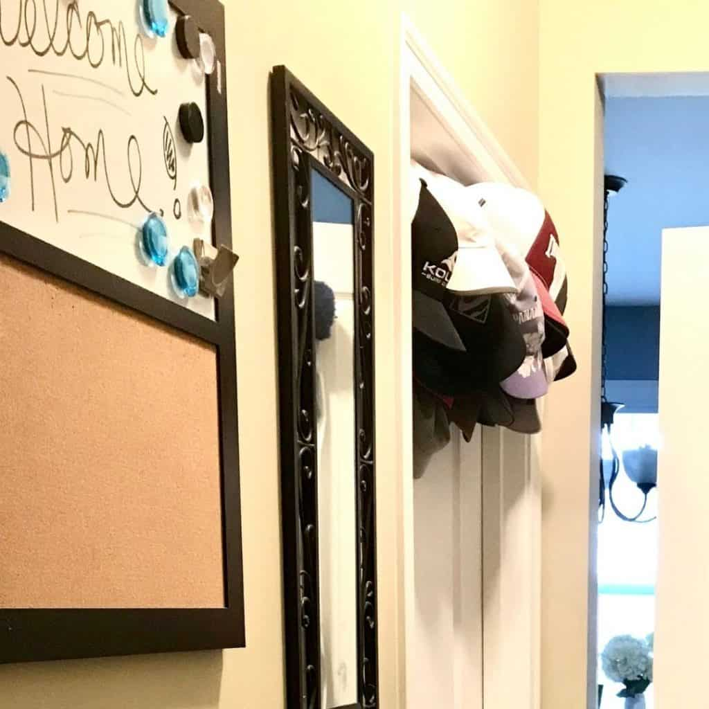 turning closet into mudroom with a message board, mirror, and over the door ball cap hooks