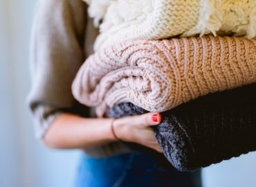 woman carrying sweaters