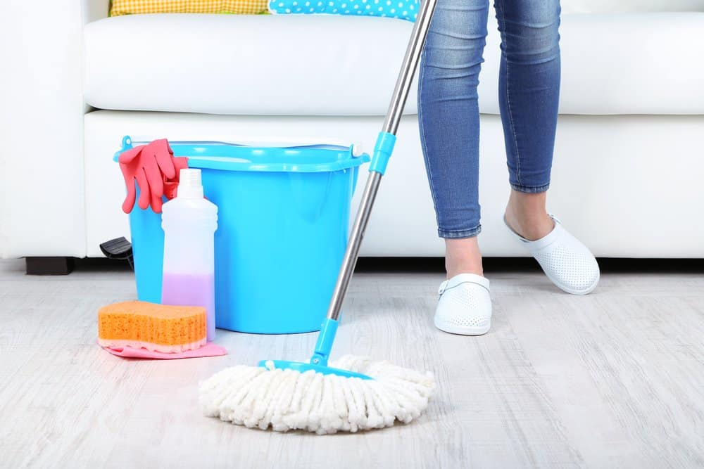 blue bucket, soap and woman pushing a mop