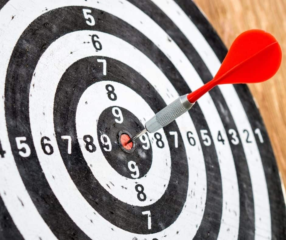 black and white target with an arrow on the bullseye