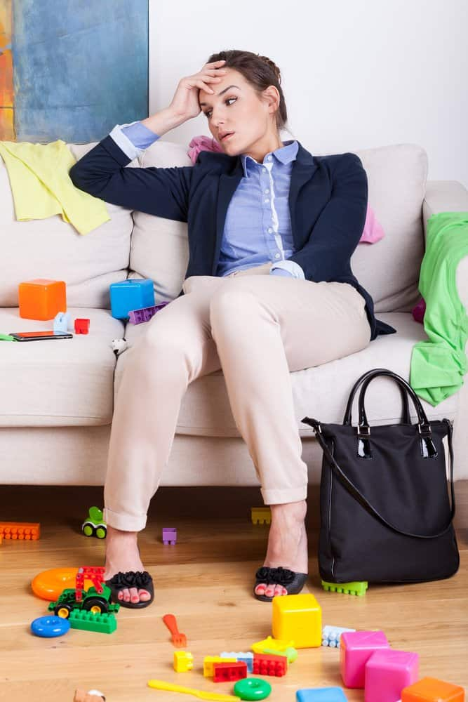 overwhelmed woman sitting on a couch in a messy room
