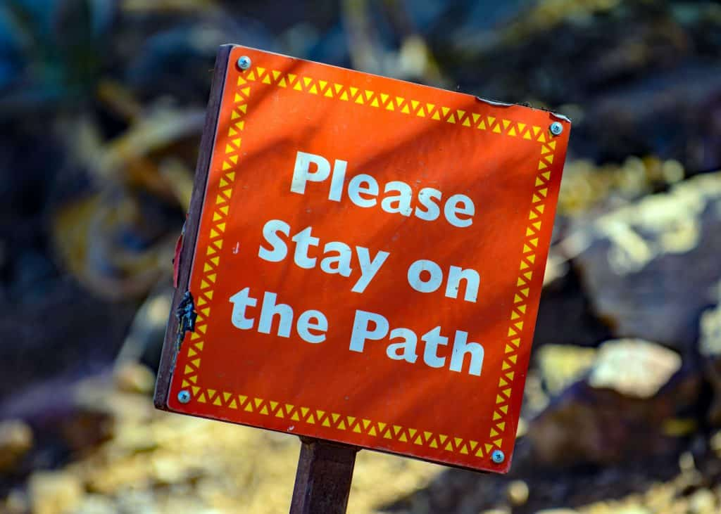 orange sign that says please stay on the path so you can stay organized and not become overwhelmed again