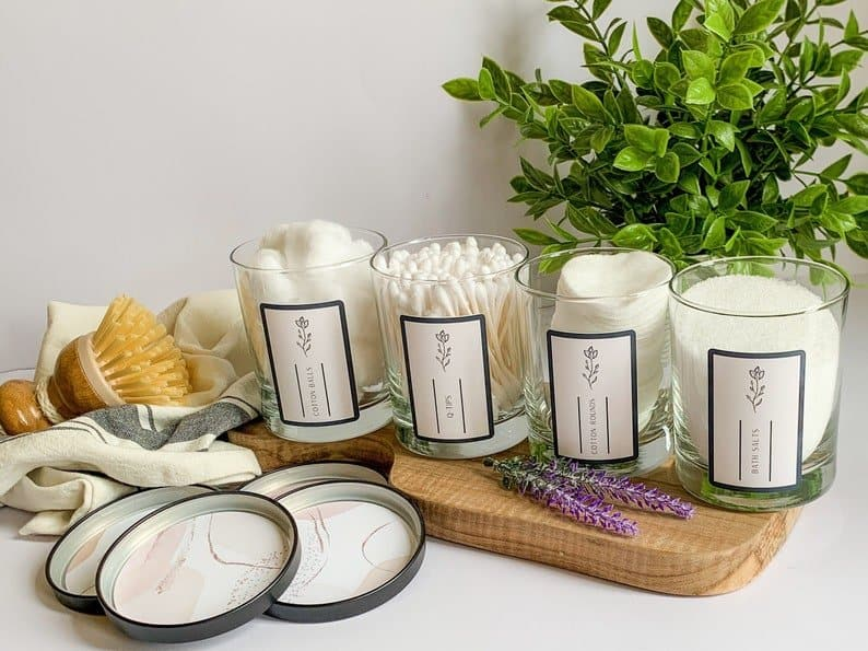 four bathroom storage jars that are labeled