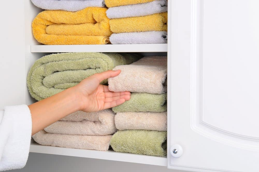 well organized towels in the colors of yellow green and tan stacked horizontally in a white bathroom cabinets