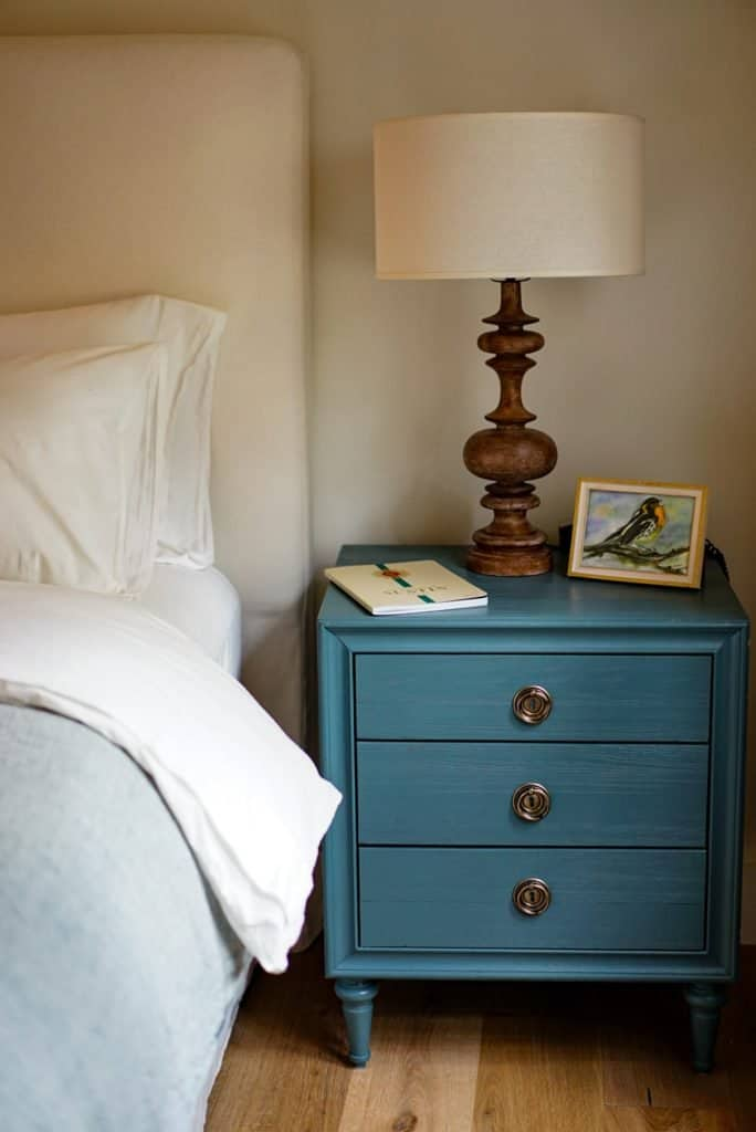 teal organized nightstand with brown light base a photograph, and notebook next to a bed