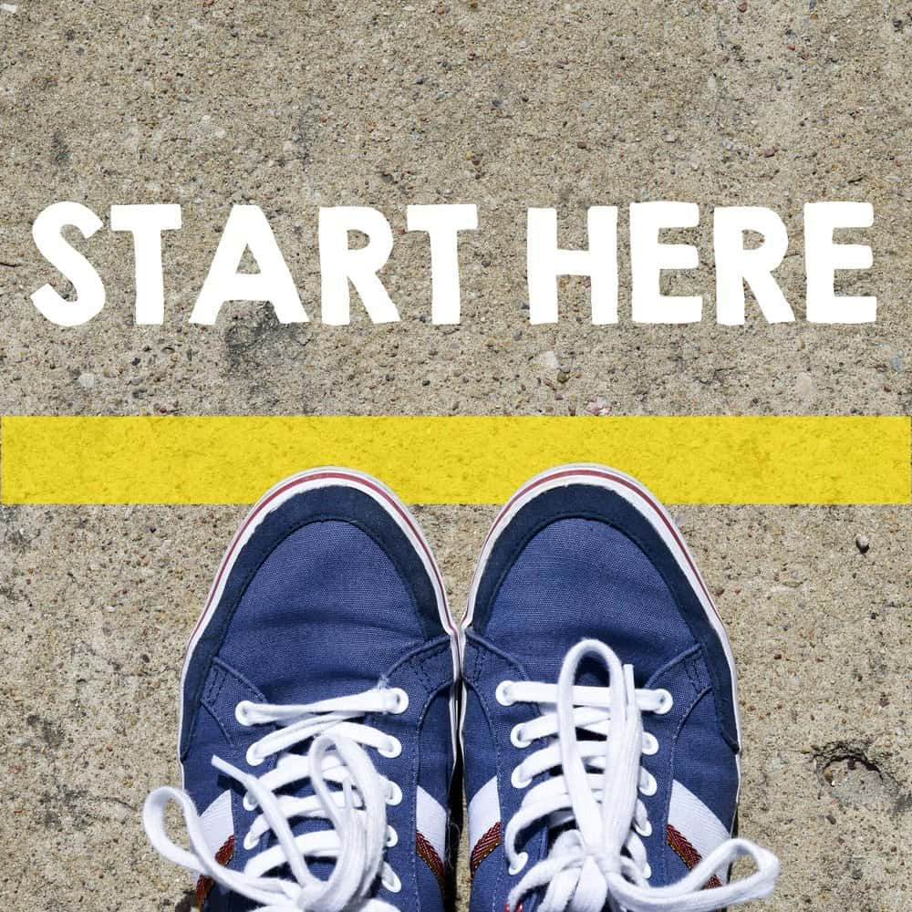 start here in white with a yellow starting line and a pair of blue shoes