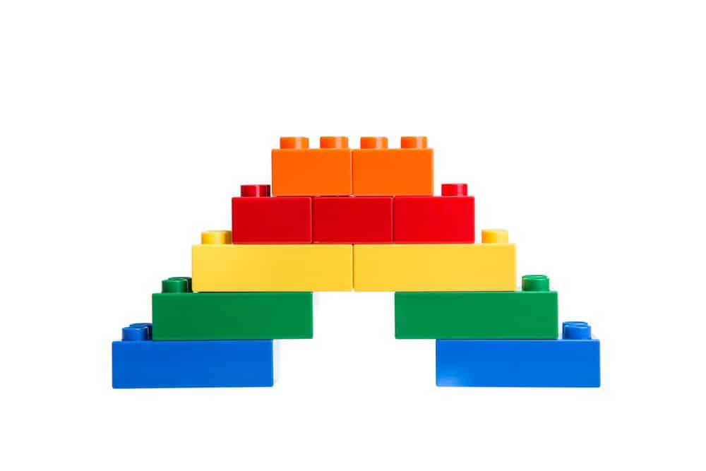 multi colored legos stacked in an arch on white background