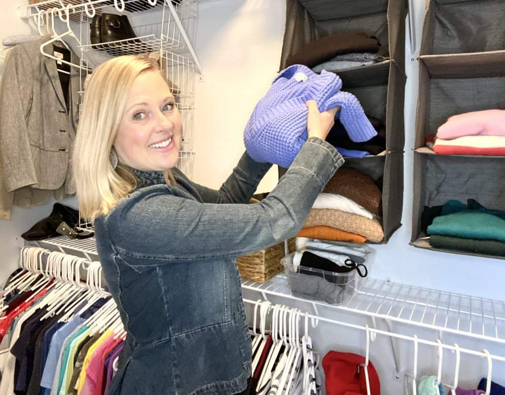 Julie Hazard putting away a blue sweater in an organized color coded closet