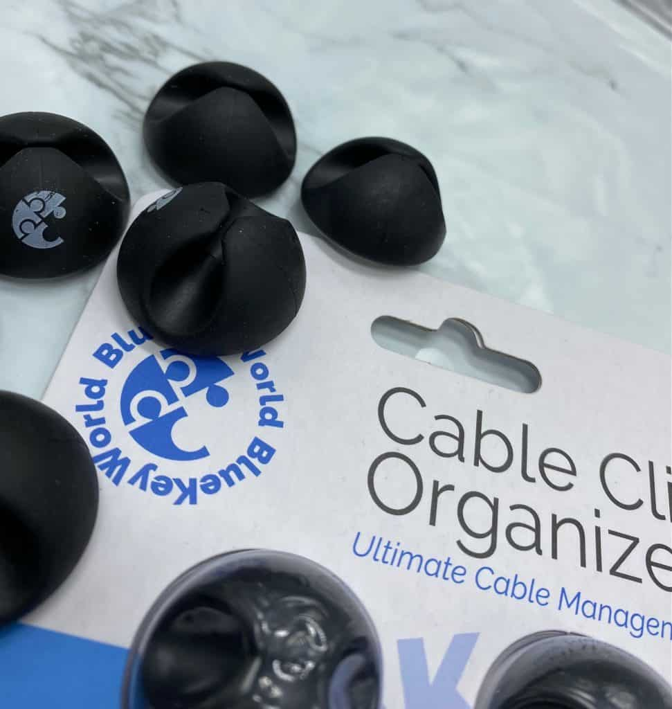 close up view of black wire holders laying on white package for bluekey world cable clip organizers