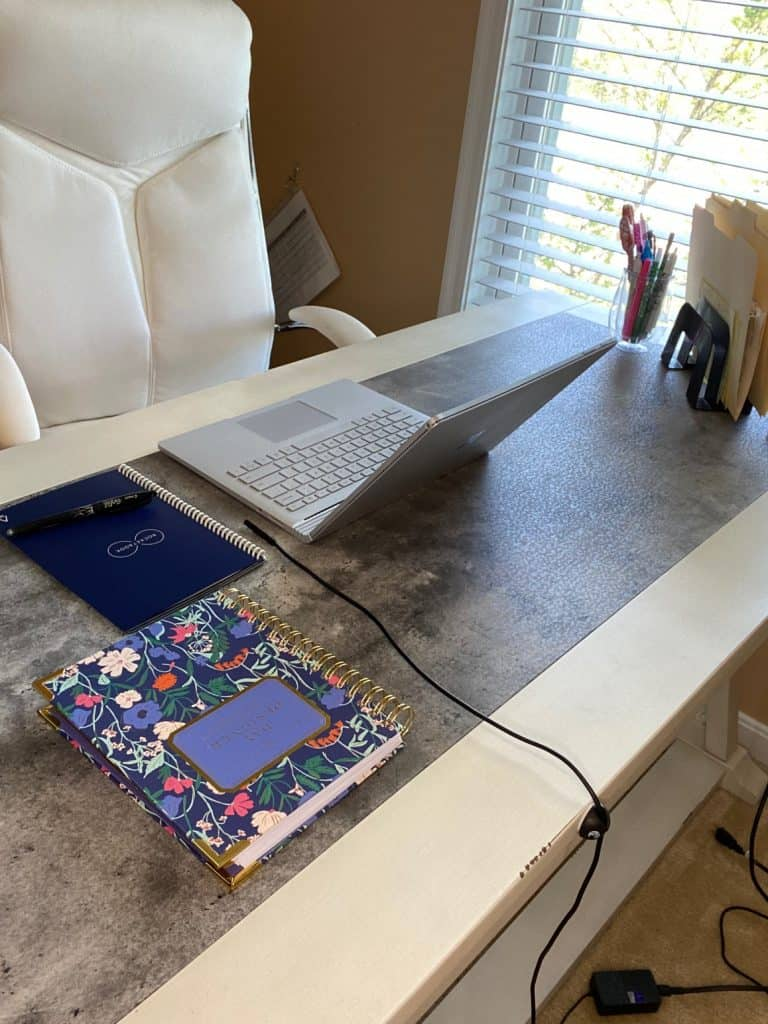 feature image of desk with laptop and two notebooks and a wire being held in place by a wire holder