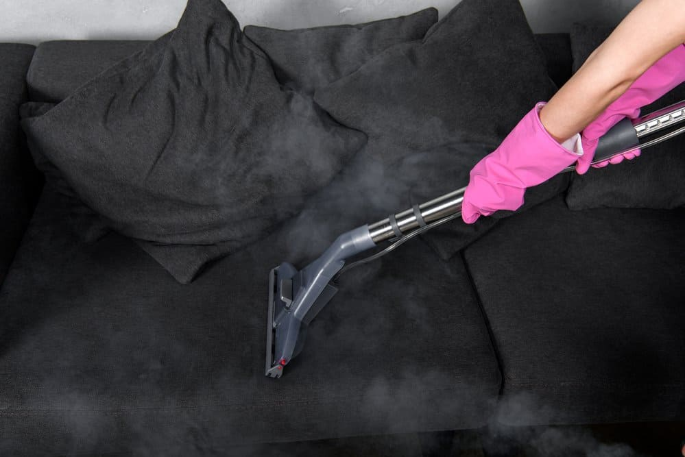 dirty black couch being cleaned with steam cleaner