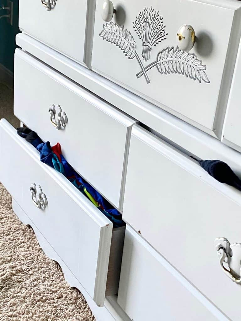 things hanging out of white dresser drawers