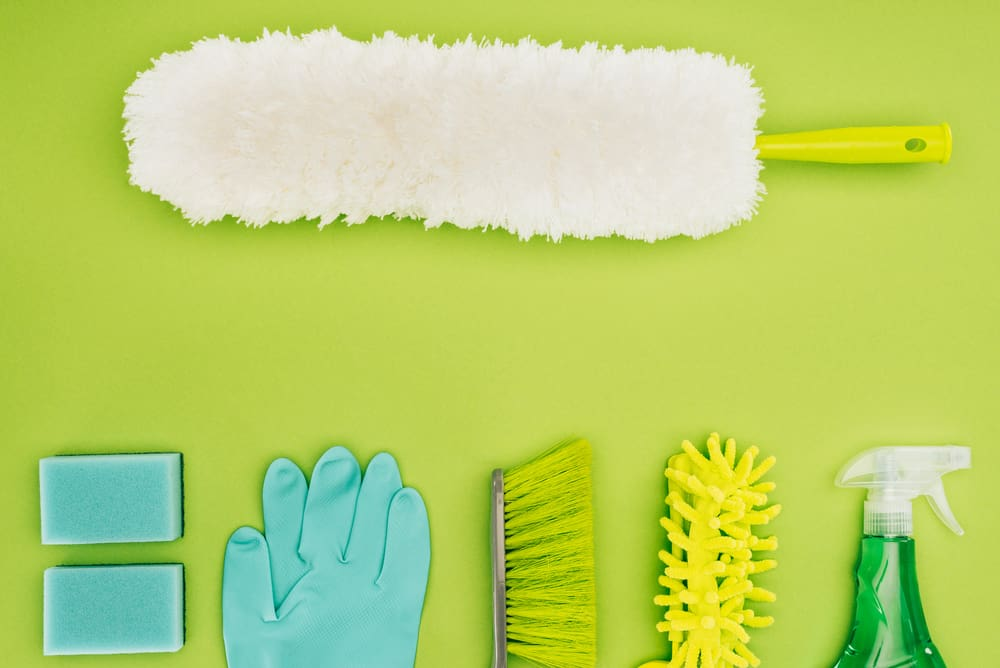cleaning supplies on green background