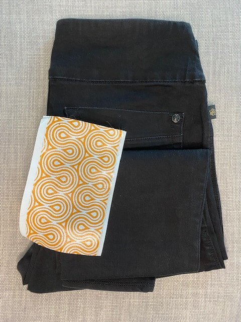 clean black pants with no lint and removed piece of orange and white lint roller tape